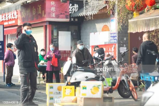 chinees die chirurgisch masker op telefoon draagt - china coronavirus stockfoto's en -beelden