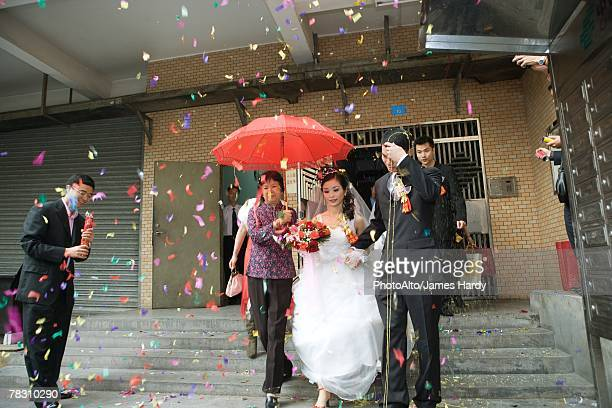 Chinese wedding, bride and groom leaving under confetti, bride covered by red parasol