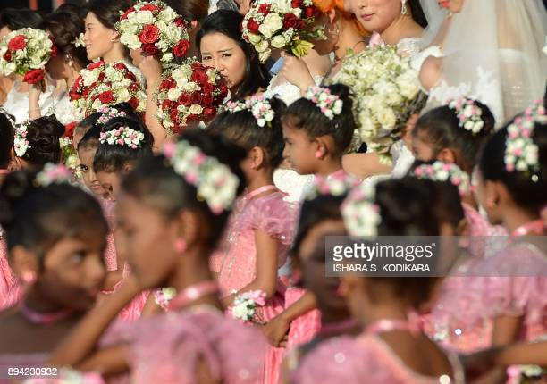 TOPSHOT Chinese wedding couple and flower girls take part in a mass wedding ceremony of 50 Chinese couples in Colombo on December 17 2017 / AFP PHOTO...