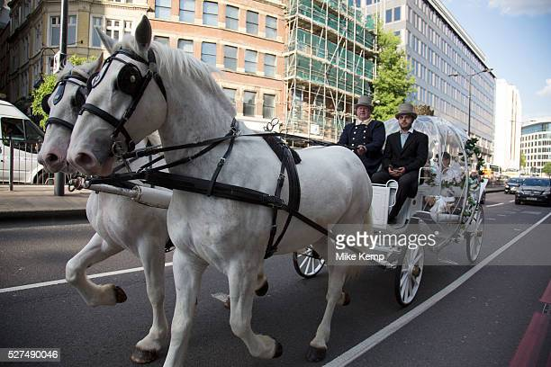 Chinese wedding couple in a horse drawn Cinderella carriage on Lower Thames Street in London UK It is a common site now to see extravagant and visual...