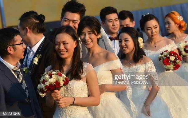 Chinese wedding couple look on as they take part in a mass wedding ceremony of 50 Chinese couples in Colombo on December 17 2017 / AFP PHOTO / ISHARA...
