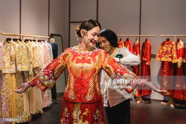 chinese wedding dress designer fitting bride in studio - phoenix bird stock pictures, royalty-free photos & images