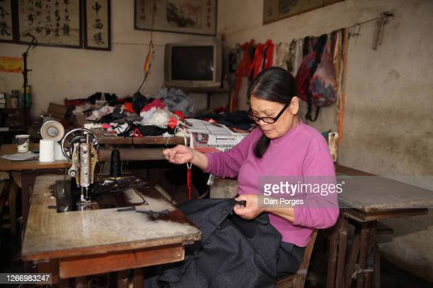 Chinese woman a taylor is sewing a pear of pants using thread and needle in front of her is a sewing machine and all around one sees sewing material...