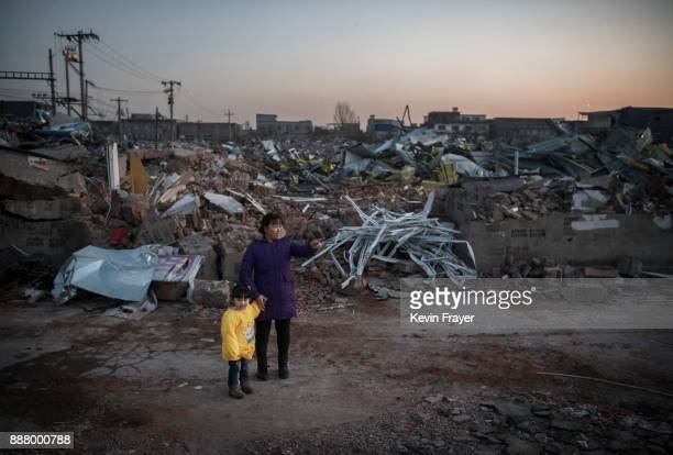 Chinese woman and child survey buildings demolished by authorities in an area that used to have migrant housing and factories on December 6 2017 in...