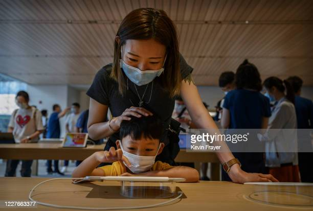 Chinese woman and her child try an ipad at the official opening of the new Apple Store in the Sanlitun shopping area on July 17 2020 in Beijing China...