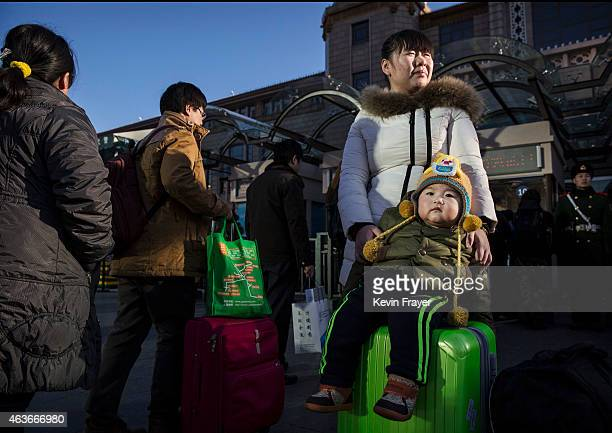 Chinese woman and her son wait in line with others as they leave for the Spring Festival at a local railway station on February 17 2015 in Beijing...