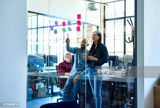chinese woman and male colleague in office with adhesive notes - black man bulge stock pictures, royalty-free photos & images