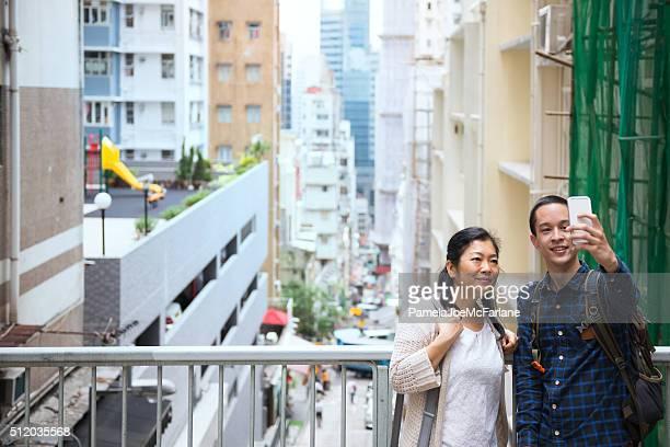 Chinese Woman and Man Taking Selfie, Mid-Levels Neighbourhood, Hong Kong