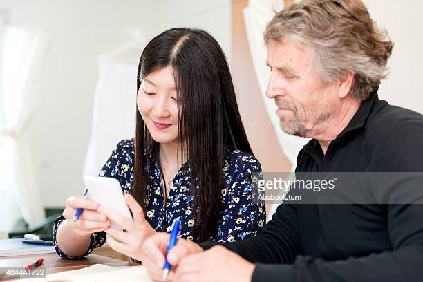 Chinese Woman and Srenior Caucasian Studying at Home, Slovenia, Europe