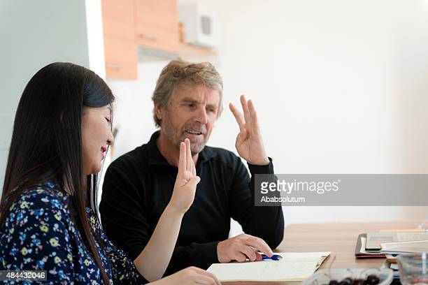 chinese woman and srenior caucasian studying chinese numbers, slovenia, europe - koper stock photos and pictures