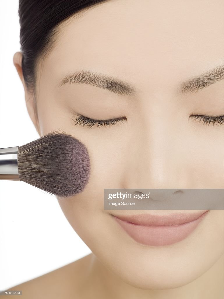 Chinese woman applying blusher : Stock Photo