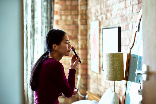 Chinese woman applying blusher with brush and looking in mirror - gettyimageskorea