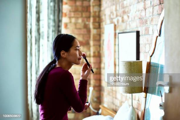 chinese woman applying blusher with brush and looking in mirror - hair back stock pictures, royalty-free photos & images