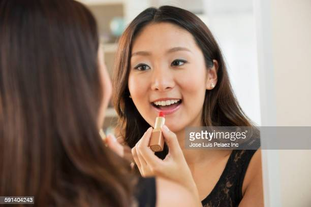 Chinese woman applying makeup in mirror