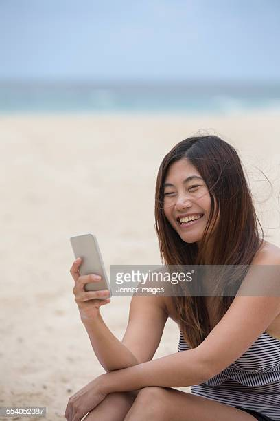 Chinese woman at beach using her smart phone.