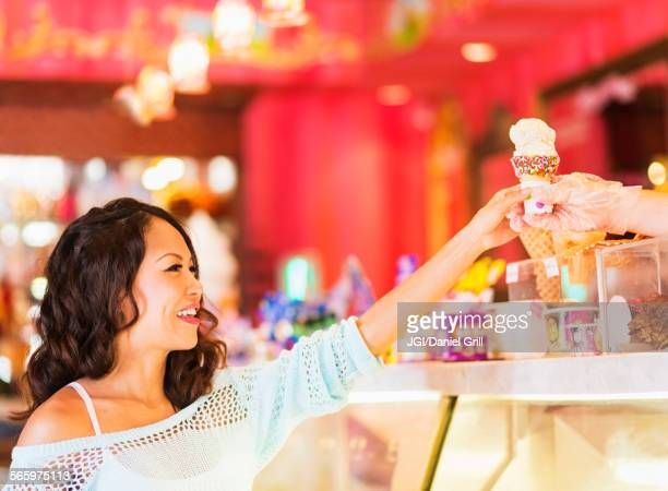 Chinese woman buying ice cream cone in shop