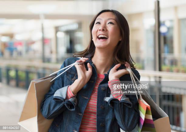 Chinese woman carrying shopping bags in mall