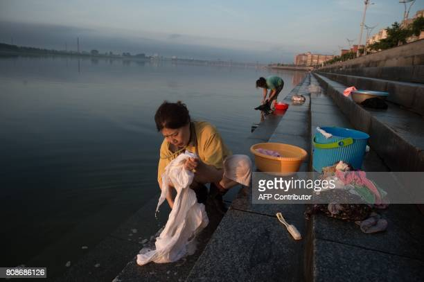 Chinese woman clean their clothes near the Friendship bridge on the Yalu River connecting the North Korean town of Sinuiju and Dandong in Chinese...