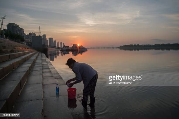 A Chinese woman cleans her clothes near the Friendship bridge on the Yalu River connecting the North Korean town of Sinuiju and Dandong in Chinese...