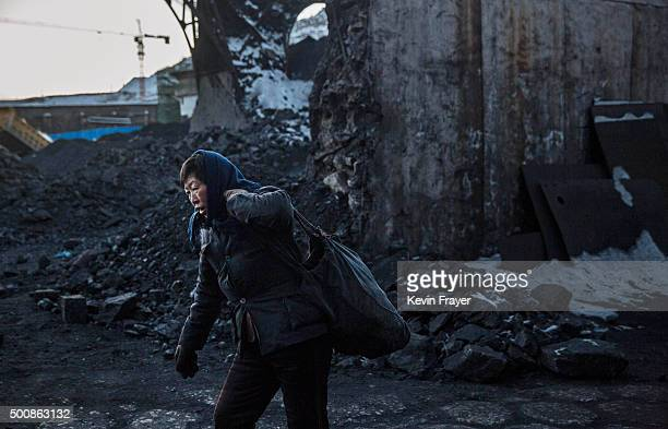 A Chinese woman collects coal in a sorting area at a coal mine on November 25 2015 in Shanxi China A history of heavy dependence on burning coal for...