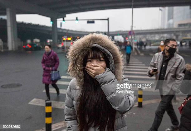 A Chinese woman covers her mouth and nose to protect against pollution as she walks to work on December 9 2015 in Beijing China The Beijing...