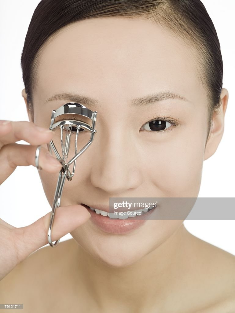 Chinese woman curling her eyelashes : Stock Photo