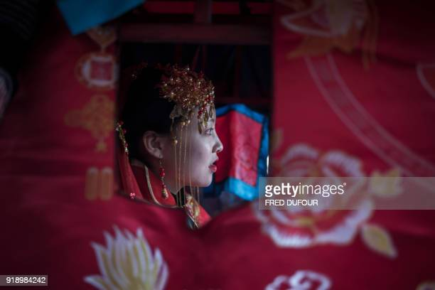 Chinese woman dressed like a traditional bride attends a wedding performance as part of the She Huo festival to celebrate the Lunar New Year marking...