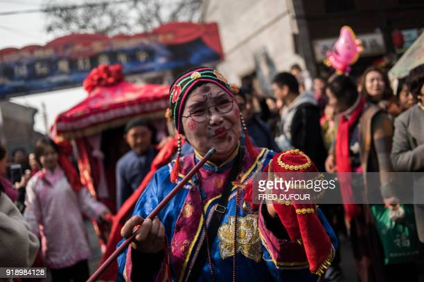 Chinese woman dressed with a traditional costume attends a wedding performance as part of the She Huo festival to celebrate the Lunar New Year...