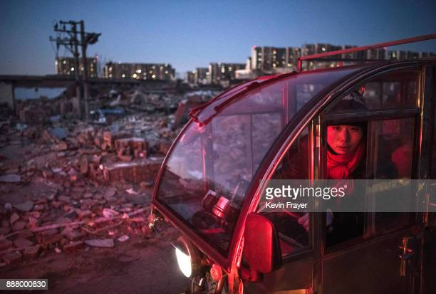 Chinese woman drives passed the rubble of buildings demolished by authorities in an area that used to have migrant housing and a clothing market on...