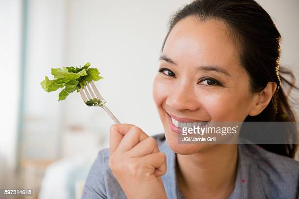 Chinese woman eating salad