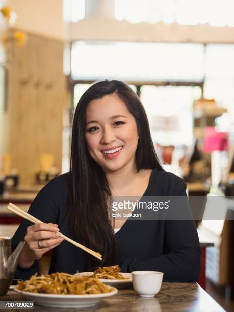 Chinese woman eating with chopsticks in restaurant