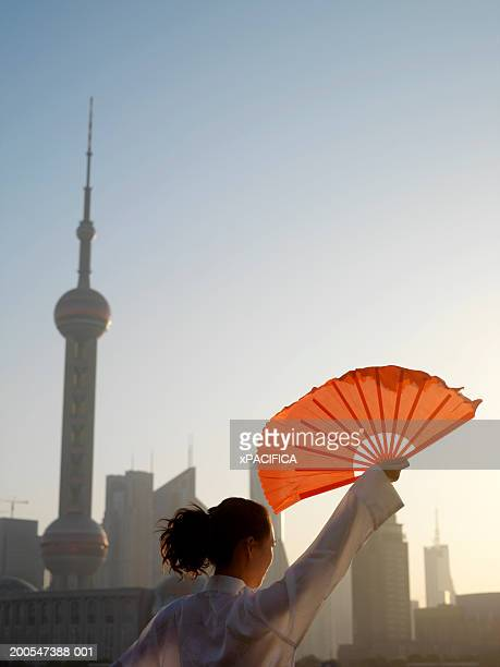 Chinese woman fan dancing in front of Pudong skyline