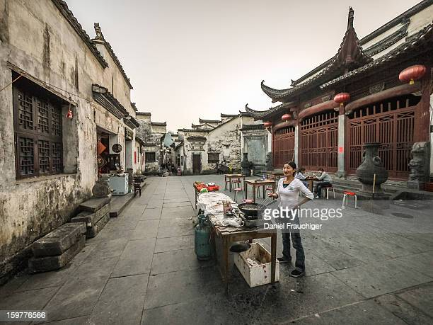 CONTENT] Chinese Woman frying and selling food on ancient Xidi market square In Xidi Anhui China September 28 2011
