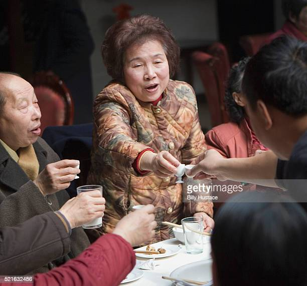 Chinese woman gives a traditional celebration toast during a Chinese New Year dinner.