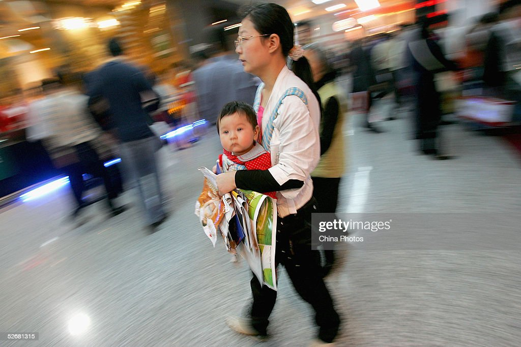 A Chinese woman holding her baby and leaflets of new commercial buildings visits a real estate fair on April 21, 2005 in Chengdu of Sichuan Province, China. China's economy grew by an unexpectedly high 9.5 percent in the first three months of this year from a year earlier, the government said on April 20, warning that it needs to tighten controls on surging investment in new factories and real estate.