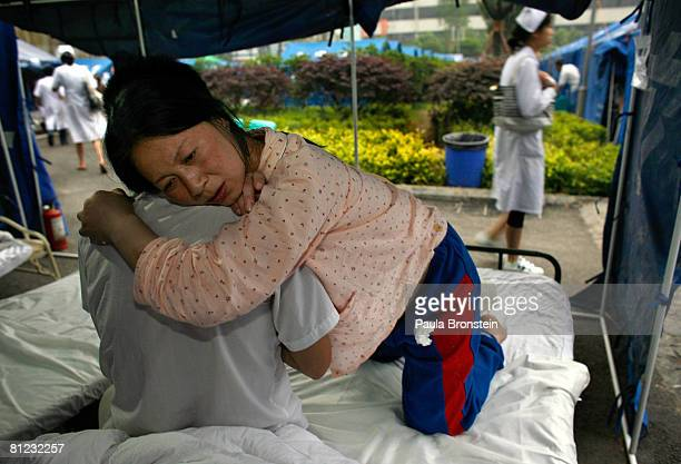 Chinese woman holds her husband while in labor about to give birth in a tented hospital camp outside the Mianyan Center hospital where patients are...