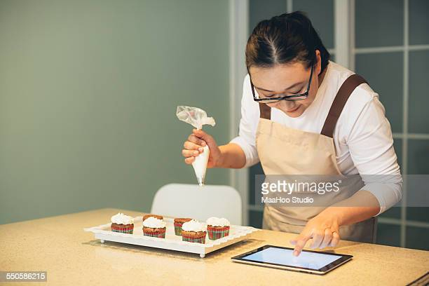 Chinese woman icing cupcakes and using iPad