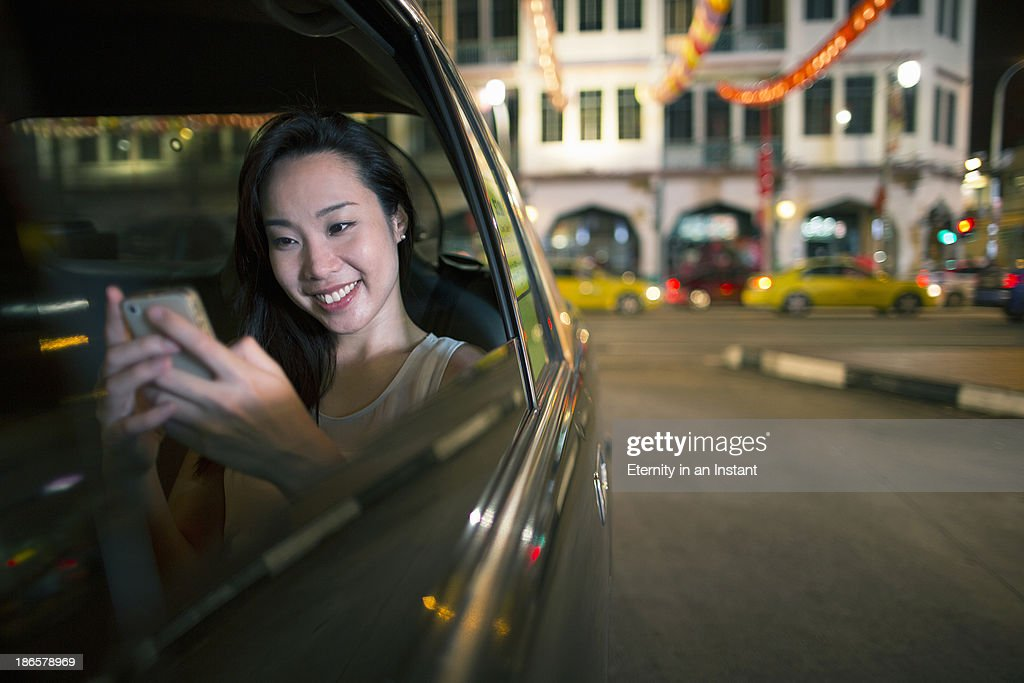 Chinese woman in car with smartphone : Stock Photo