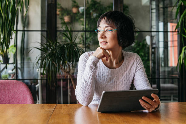 chinese woman in her 60s using tablet with hand on chin - old asian woman stock pictures, royalty-free photos & images