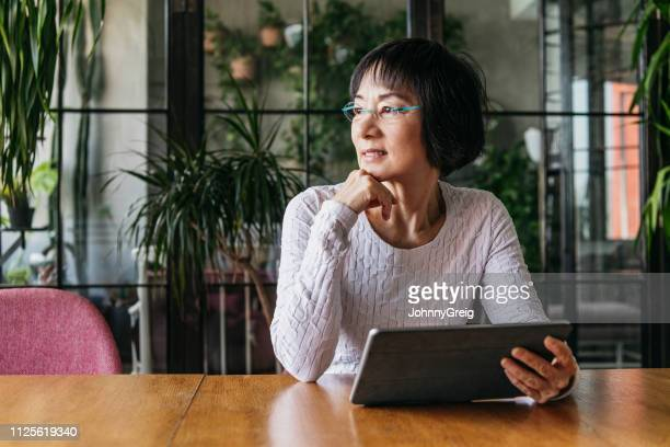 chinese woman in her 60s using tablet with hand on chin - adult movies stock pictures, royalty-free photos & images