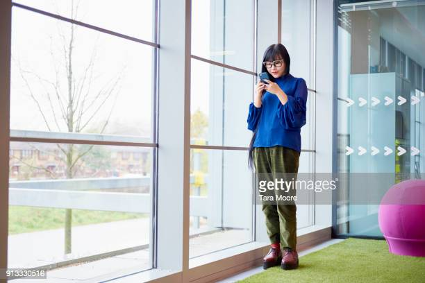 chinese woman in office looking at mobile phone - somente adultos - fotografias e filmes do acervo
