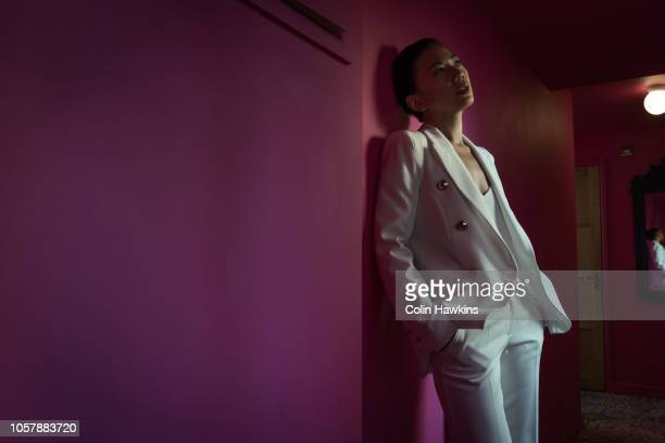 chinese woman in white suit interior - androgyn stock-fotos und bilder