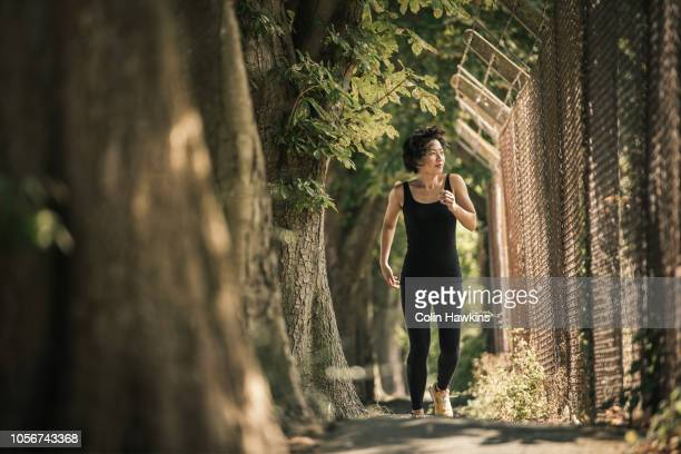 Chinese woman jogging in industrial area