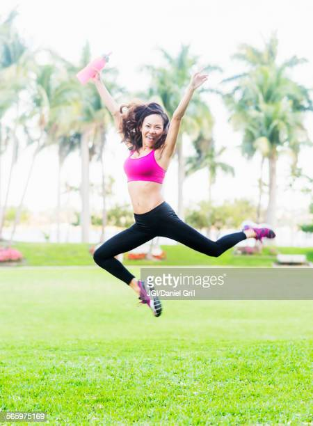 Chinese woman jumping for joy in park