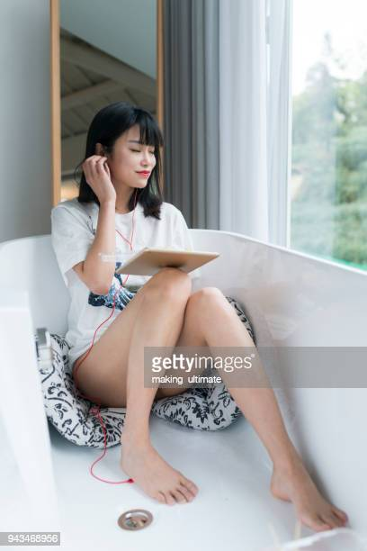 Chinese Woman listening to music in bathtub