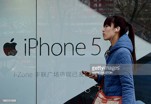 A Chinese woman listens to her iPhone outside an Apple reseller store in Beijing on April 2 2013 Apple chief executive Tim Cook has apologised to...