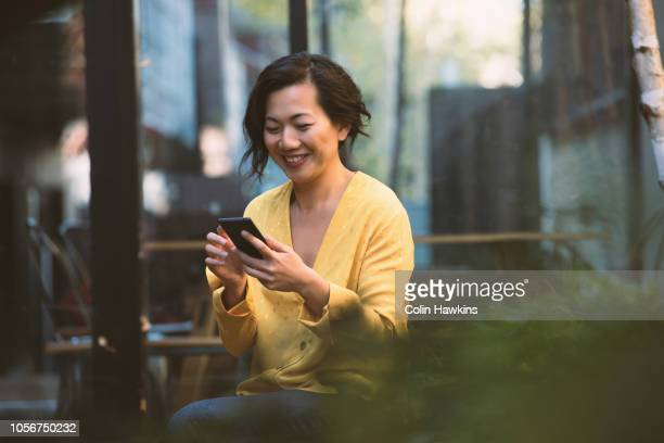 Chinese woman looking at mobile phone outside