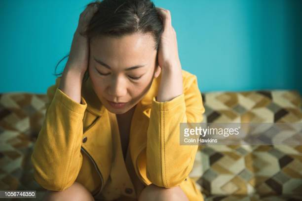 Chinese woman looking stressed with head in hands