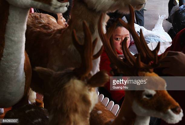Chinese woman looks at Christmas decorations outside a store on December 19 2008 in Beijing China A large number of Christmas decorations destined to...