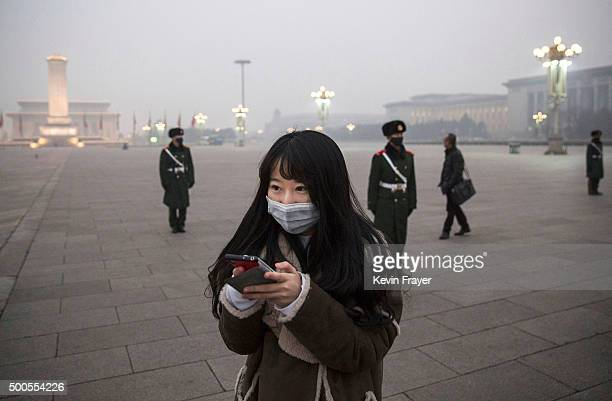 Chinese woman looks at her phone as Chinese Paramilitary police wear masks to protect against pollution as they stand guard during smog in Tiananmen...